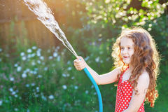 Little girl watering plant in garde stock image