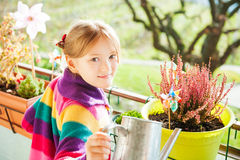 Little girl watering plants on the balcony Stock Photos
