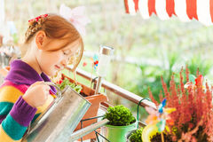 Little girl watering plants on the balcony Royalty Free Stock Photography