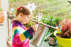 Little girl watering plants on the balcony Stock Images