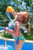 Little girl watering at the pool Stock Photos