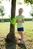 Little girl watering tree Stock Image