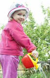 A little girl watering with watering cloth. A little girl in a pink jacket watering with watering cloth Stock Image