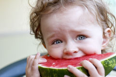 Little girl with watermelon. Little toddler eating melon, outdoor photo Royalty Free Stock Photography