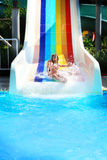 Little girl on a waterslide in aquapark. Funny photo of cute girl on a waterslide in aquapark in vacation sunny day Stock Image