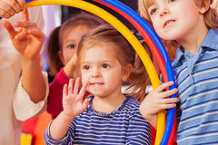 Little girl wave hand looking though hoop Stock Photography