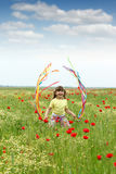 Little girl waving with colorful ribbons on meadow Royalty Free Stock Photography