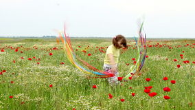 Little girl waving with colorful ribbons on meadow Royalty Free Stock Image