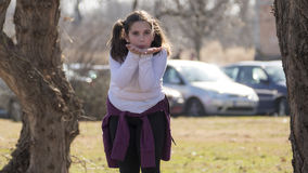 Little girl waving in park. During the sunny spring day Royalty Free Stock Photos