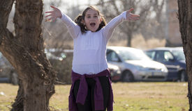 Little girl waving in park. During the sunny spring day Stock Photography