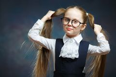 Little Girl Wear Glasses Look at Camera. Child Hold Hand on Ponytail royalty free stock images