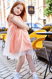 Little girl wear peach color fashion dress. Little girl pretty face smile happy wear peach color fashion dress sit in cafe yellow chair on the street city summer stock photography