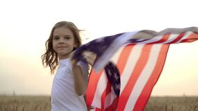 Little Girl wearing an American flag while running in a beautiful wheat field on sunset
