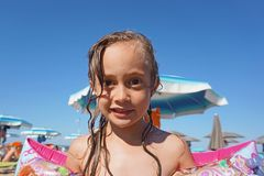 Little girl wearing arm floats on the beach stock photo