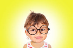 Little girl wearing black glasses looking at camera. Portrait of smiling little girl wearing black glasses looking at camera. Yellow background royalty free stock photos
