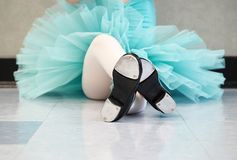 Little girl wearing a tutu and tap shoes in her tap dance class. Little girl wearing a blue tutu and tap shoes in her tap dance class sitting cross-legged royalty free stock images