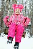 Little girl wearing bright clothes is swinging on a swing outdoors in winter. Park Stock Images