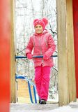 Little girl wearing bright pink clothes on the playground outdoors in winter. Park Stock Image