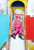 Little girl wearing bright pink clothes on the playground in winter. Park Royalty Free Stock Photography