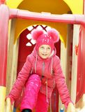 Little girl wearing bright pink clothes plays on the playground outdoors in winter. Park Royalty Free Stock Photos