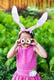 Little Girl Wearing Bunny Ears and Silly Egg Eyes. A funny portrait of a little girl having fun on Easter wearing bunny ears and holding up silly eyes made from Stock Photo