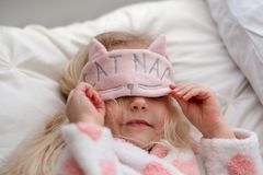 Little girl wearing cat nap mask stock photography