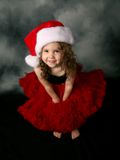 Little girl wearing Christmas santa hat and skirt. Beautiful young female child wearing a santa hat and red tutu skirt Royalty Free Stock Photography
