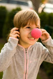 Little girl wearing clown nose Stock Images