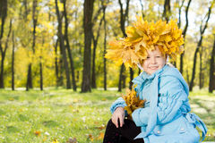 Little girl wearing a crown of autumn leaves Stock Images