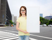 Little girl wearing eyeglasses with blank board. Vision, health, advertisement and people concept - smiling little girl wearing eyeglasses with white blank board stock images