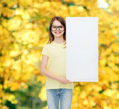 Little girl wearing eyeglasses with blank board. Vision, health, advertisement and people concept - smiling little girl wearing eyeglasses with white blank board royalty free stock images