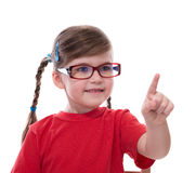 Little girl wearing glasses and pointing by forefinger to somewh Royalty Free Stock Images