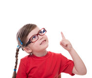 Little girl wearing glasses and pointing by forefinger to somewh. Ere up isolated on white Stock Images