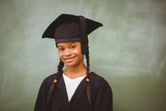Little girl wearing graduation robe Stock Photos