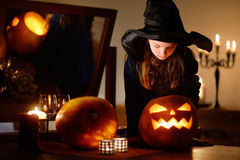 Little girl wearing halloween costume playing with a pumpkin Royalty Free Stock Photo