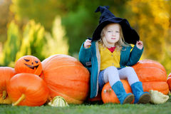 Little girl wearing halloween costume on a pumpkin patch Royalty Free Stock Photo