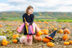 Little girl wearing halloween witch costume on pumpkin patch Stock Photos