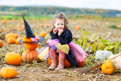 Little girl wearing halloween witch costume on pumpkin patch Royalty Free Stock Photos