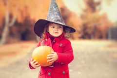 Little girl wearing Halloween witch hat and warm red coat, having fun in autumn day. Royalty Free Stock Photography