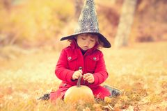 Little girl wearing Halloween witch hat and warm red coat, having fun in autumn day. Royalty Free Stock Photos