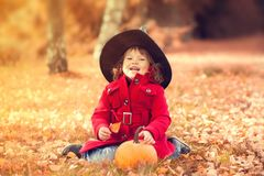Little girl wearing Halloween witch hat and warm red coat, having fun in autumn day. Royalty Free Stock Images