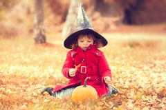Little girl wearing Halloween witch hat and warm red coat, having fun in autumn day. Stock Image