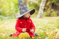 Little girl wearing Halloween witch hat and warm red coat, having fun in the park, autumn day. Royalty Free Stock Image