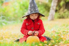 Little girl wearing Halloween witch hat and warm red coat, having fun in the park, autumn day. Stock Photo