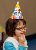 Little girl wearing a Happy Birthday hat Stock Images
