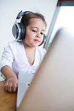 Little girl wearing headphones while looking at laptop at table in house Royalty Free Stock Photos