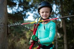 Little girl wearing helmet standing near zip line. In the forest stock photo