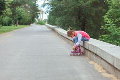 Little girl sitting on parapet and putting on rollers in the park. Little girl wearing jeans and jacket sitting on parapet and putting on rollers in the park in Stock Image