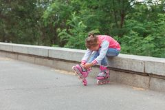 Little girl sitting on parapet and putting on rollers in the park. Little girl wearing jeans and jacket sitting on parapet and putting on rollers in the park in Royalty Free Stock Images