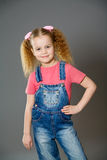 Little girl wearing jeans overalls Stock Image